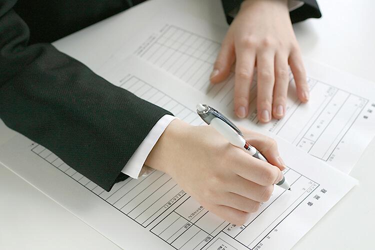 スーツを着た女性が履歴書を書いている写真