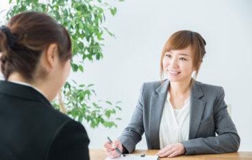 ジャケットを着ている女性が書類を使って説明をしている