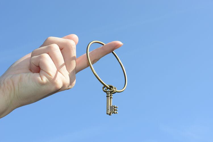 青空の下鍵を人差し指に通して掲げている写真