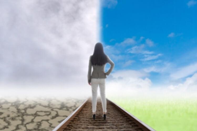 女性が2つの道どちらに進むか悩んでいる写真