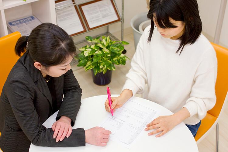 スーツを着た女性が求職者の女性に書類に関して指導をしている写真
