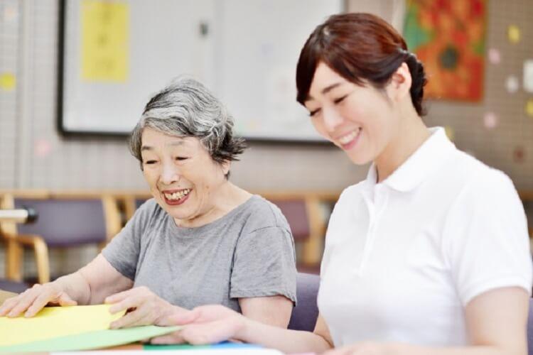 女性の介護士がご老人と本を見ている写真