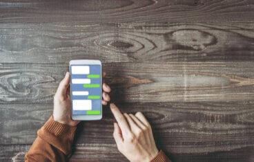 茶色の服を着た人がスマートフォンでメッセージを確認している写真